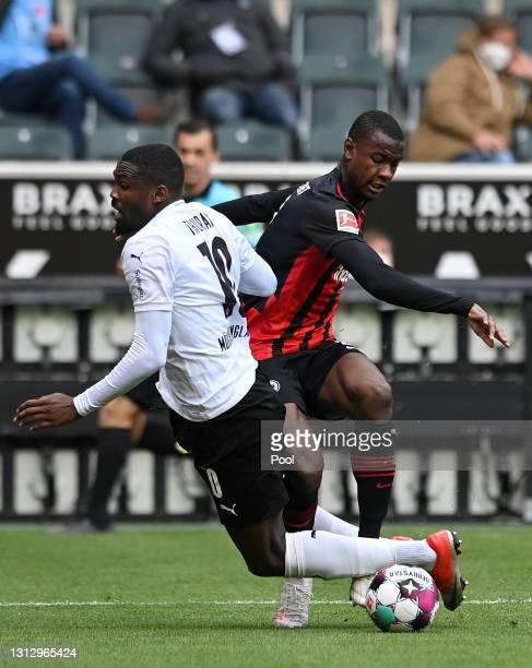 Marcus Thuram of Borussia Moenchengladbach battles for possession with Evan Ndicka of Eintracht Frankfurt during the Bundesliga match between...