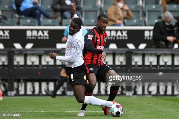 Marcus Thuram of Borussia Moenchengladbach is challenged by Evan Ndicka of Eintracht Frankfurt during the Bundesliga match between Borussia...