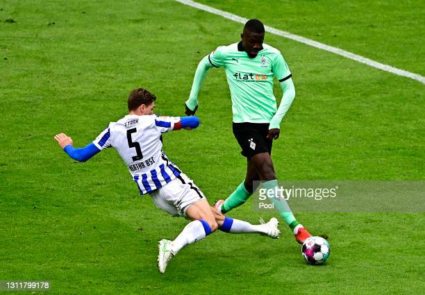 Marcus Thuram of Borussia Moenchengladbach is fouled by Niklas Stark of Hertha Berlin leading to a penalty during the Bundesliga match between Hertha...