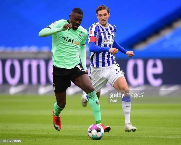 Marcus Thuram of Borussia Moenchengladbach is put under pressure by Niklas Stark of Hertha Berlin during the Bundesliga match between Hertha BSC and...
