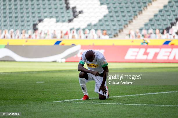 Marcus Thuram of Borussia Moenchengladbach takes a knee after after he scores his Teams second goal during the Bundesliga match between Borussia...