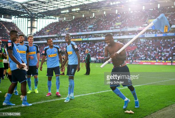 Marcus Thuram of Borussia Monchengladbach holds a corner flag as he celebrates victory with team mates after the Bundesliga match between 1 FC Koeln...