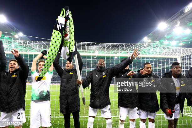 Marcus Thuram of Borussia Monchengladbach holds a corner flag as hecelebrates with his team mates during the Bundesliga match between Borussia...