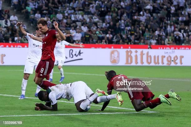 Marcus Thuram of Borussia Monchengladbach is challenged by Dayot Upamecano of Bayern Munich during the Bundesliga match between Borussia...