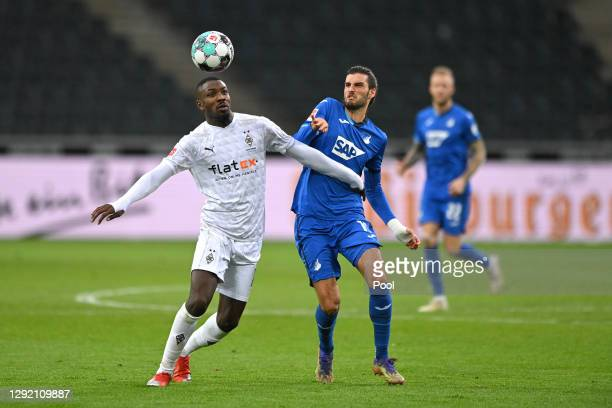 Marcus Thuram of Borussia Monchengladbach is challenged by Florian Grillitsch of Hoffenheim during the Bundesliga match between Borussia...