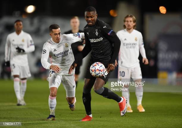 Marcus Thuram of Borussia Monchengladbach is challenged by Lucas Vazquez of Real Madrid during the UEFA Champions League Group B stage match between...