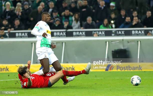 Marcus Thuram of Borussia Monchengladbach is fouled by Javi Martinez of FC Bayern Munich and a penalty is later awarded during the Bundesliga match...
