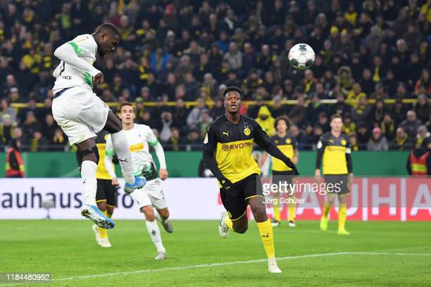 Marcus Thuram of Borussia Monchengladbach scores his team's first goal as DanAxel Zagadou of Borussia Dortmund looks on during the DFB Cup second...