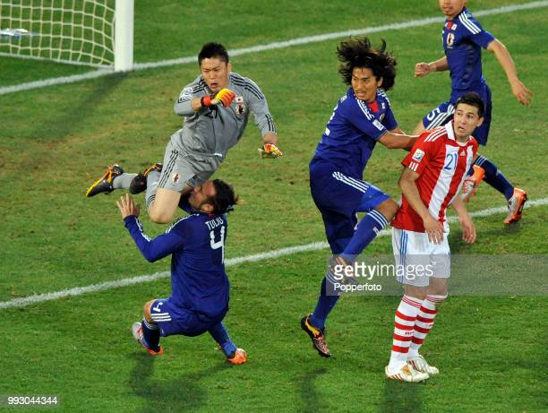 Marcus Tulio Tanaka of Japan is taken out by his goalkeeper Eiji Kawashima during the FIFA World Cup Round of 16 match between Paraguay and Japan at...