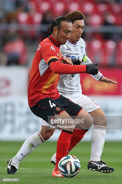 Marcus Tulio Tanaka of Nagoya Grampus and Toshihiro Aoyama of Sanfrecce Hiroshima compete for the ball during the J League match between Nagoya...