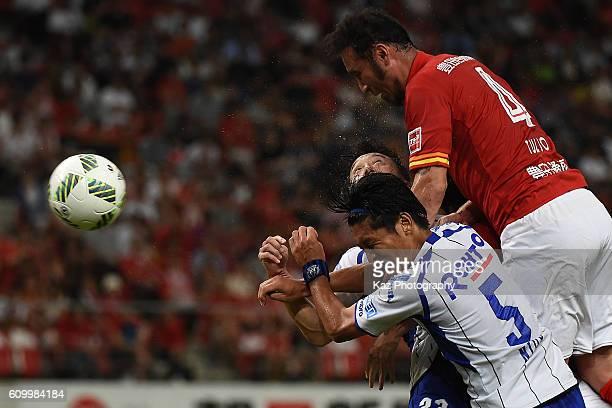 Marcus Tulio Tanaka of Nagoya Grampus wins the header over Daiki Niwa and Jae Suk Oh of Gamba Osaka during the J League match between Nagoya Grampus...