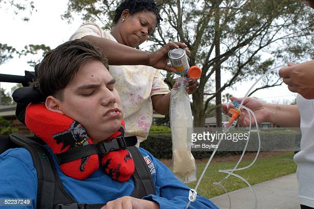 Marcus Wade receives nutrition through his feeding tube from his nurse Dee Harris outside the hospice center where Terri Schiavo the Florida woman in...
