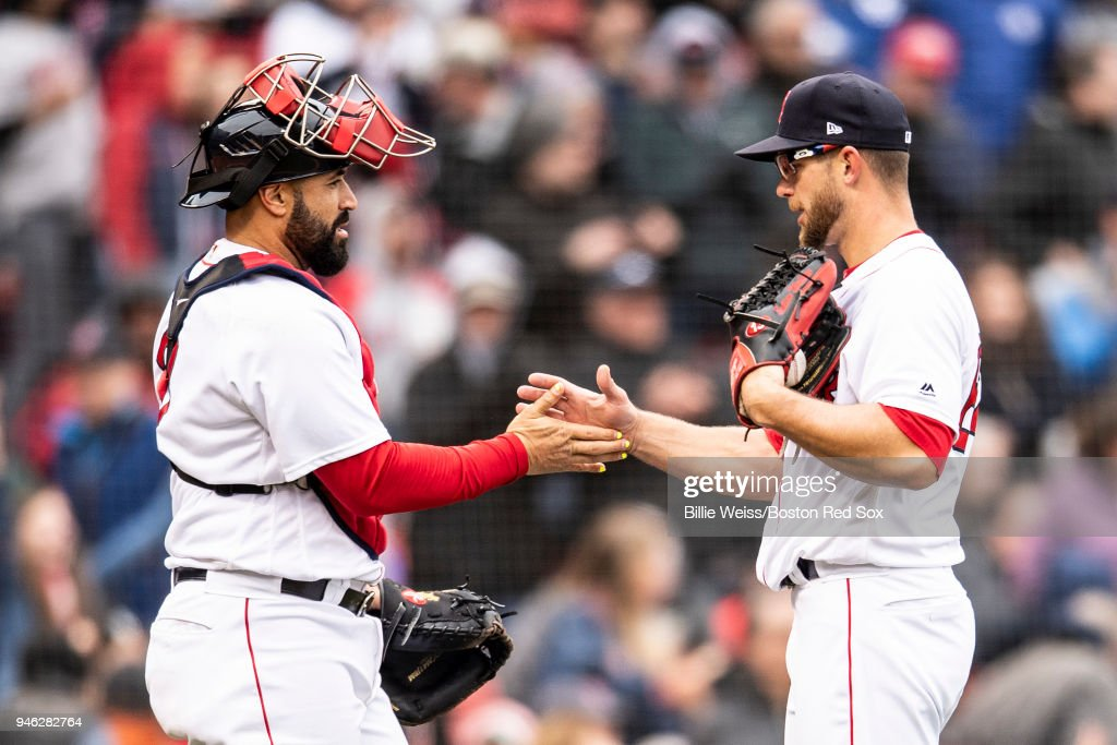 Marcus Walden #64 and Sandy Leon #3 of the Boston Red Sox celebrate after recording the final out against the Baltimore Orioles on April 14, 2018 at Fenway Park in Boston, Massachusetts.