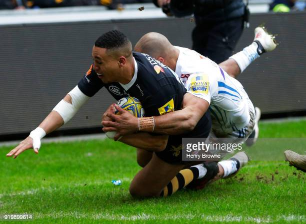 Marcus Watson of Wasps scores their first try despite the efforts of Olly Woodburn of Exeter Chiefs during the Aviva Premiership match between Wasps...