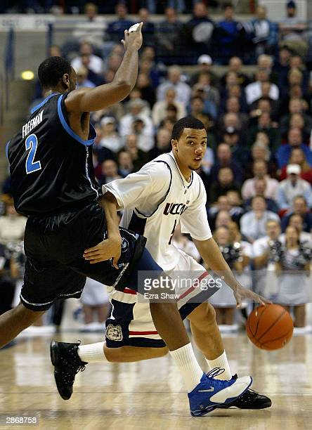 Marcus Williams of the UCONN Huskies dribbles around Courland Freeman of the Georgetown Hoyas January 14, 2004 at the Gampel Pavilion in Storrs,...