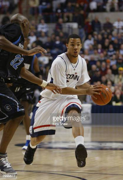 Marcus Williams of the University of Connecticut Huskies looks to pass the ball by Gerald Riley of the Georgetown Hoyas during the game on January...