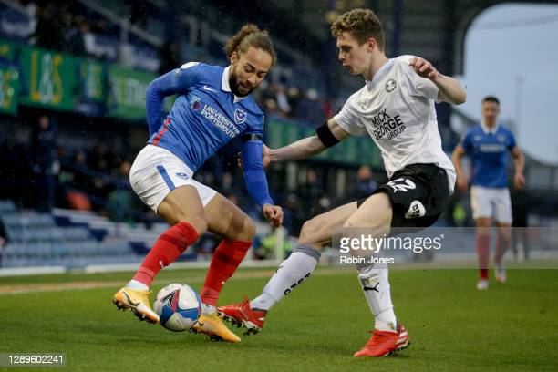 Marcuss Harness of Portsmouth FC and Ethan Hamilton of Peterborough United during the Sky Bet League One match between Portsmouth and Peterborough...