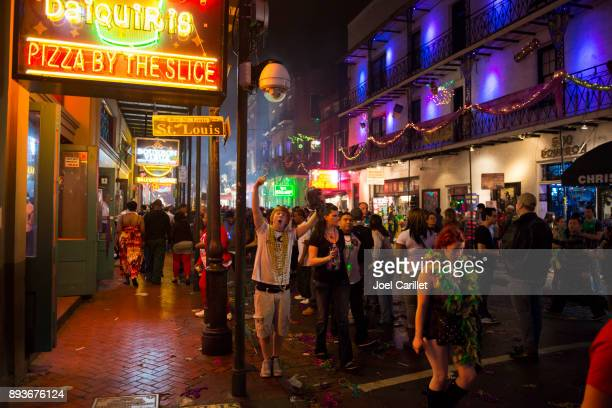 mardi gras atmosphere on bourbon street, new orleans - new orleans mardi gras stock photos and pictures
