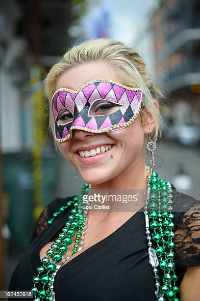 mardi gras girl with green beads and carnival mask - mardi gras beads stock photos and pictures