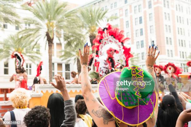 mardi gras parade spectators raise arms to catch beads - mardi gras new orleans stock photos and pictures