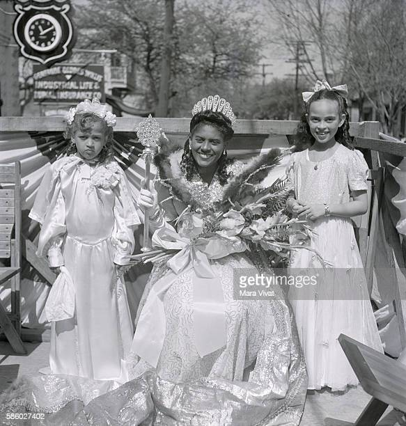 A Mardi Gras princess and two younger attendants ride a parade float wearing white gowns and holding bouquets New Orleans Louisiana circa 1950