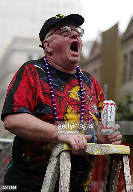 Mardi Gras reveler Patrick Donovan pauses from drinking his beer to join in the chorus of revelers calling for throws of beads February 24 2004 in...