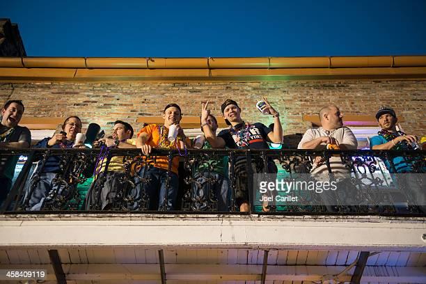 mardi gras revelers on bourbon street balcony, new orleans - mardi gras fun in new orleans stock photos and pictures
