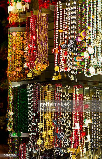 mardi grass beads on display in a store in new orleans - mardi gras beads stock photos and pictures