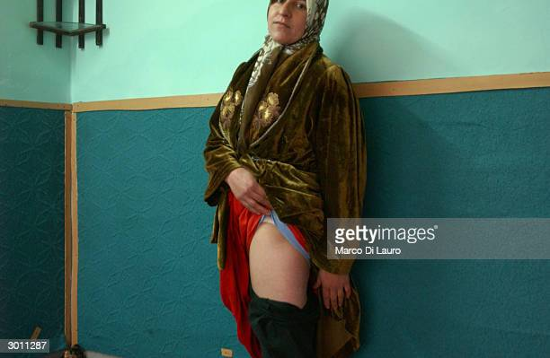 Mardin Mahmod, a victim of the March 16, 1988 chemical attacks on Halabja, shows where she was injured as she stands in her house February 24, 2004...