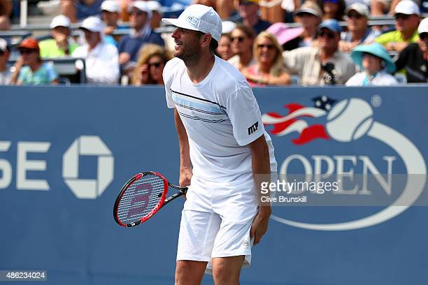 Mardy Fish of the United States holds his leg while playing against Feliciano Lopez of Spain during their Men's Singles Second Round match on Day...