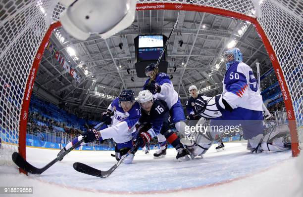 Marek Daloga of Slovakia and Ryan Donato of the United States reach for the puck at the net during the Men's Ice Hockey Preliminary Round Group B...