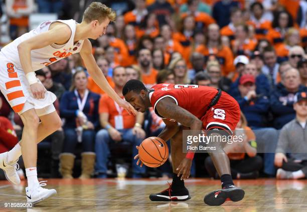 Marek Dolezaj of the Syracuse Orange hits Lavar Batts Jr #3 of the North Carolina State Wolfpack in the face while reaching for a loose ball during...