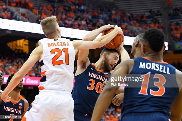 Marek Dolezaj of the Syracuse Orange reaches for the ball controlled by Jay Huff of the Virginia Cavaliers during the first half at the Carrier Dome...