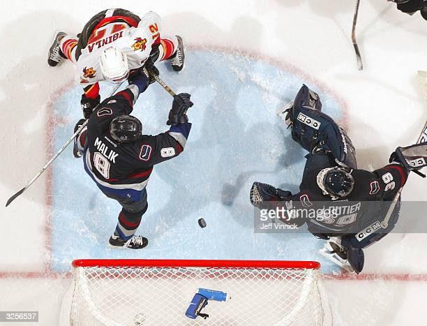 Marek Malik of the Vancouver Canucks keeps Jarome Iginla off the puck as Dan Cloutier of the Canucks watches the rebound during the third period of...