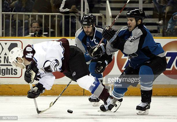 Marek Svatos of the Colorado Avalanche is checked from behind by Scott Hannan of the San Jose Sharks during game five of the Western Conference...