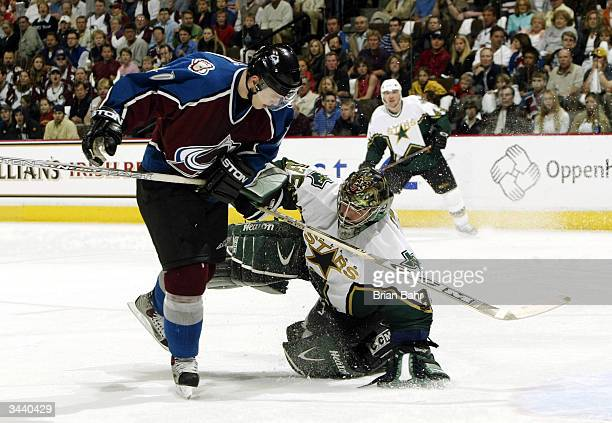Marek Svatos of the Colorado Avalanche nearly collides with goalie Marty Turco of the Dallas Stars as he thinks better of clearing the puck and...