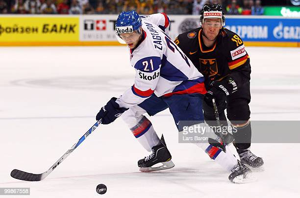 Marek Zagrapan of Slovakia is challenged by Kai Hospelt of Germany during the IIHF World Championship qualification round match between Slovakia and...