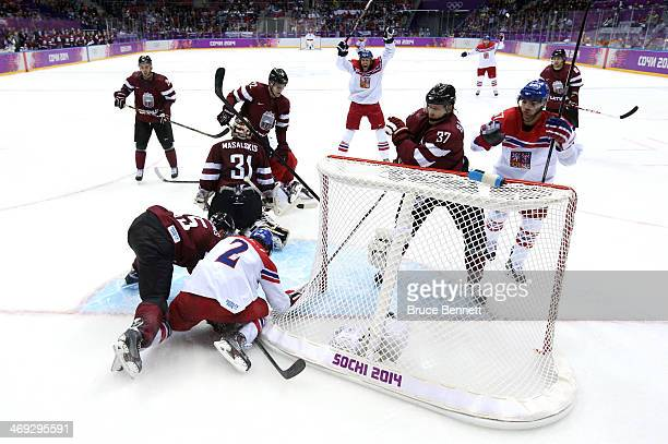Marek Zidlicky of Czech Republic scores while being hit into the net by Martins Karsums of Latvia in the second period during the Men's Ice Hockey...