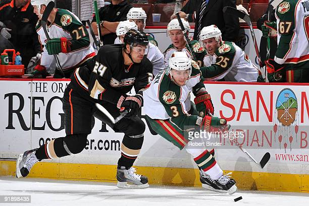 Marek Zidlicky of the Minnesota Wild chases the puck against Evgeny Artyukhin of the Anaheim Ducks during the game on October 14 2009 at Honda Center...