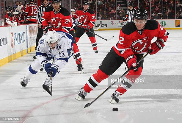 Marek Zidlicky of the New Jersey Devils plays the puck while being pursued by Tom Pyatt of the Tampa Bay Lightning during the game at the Prudential...