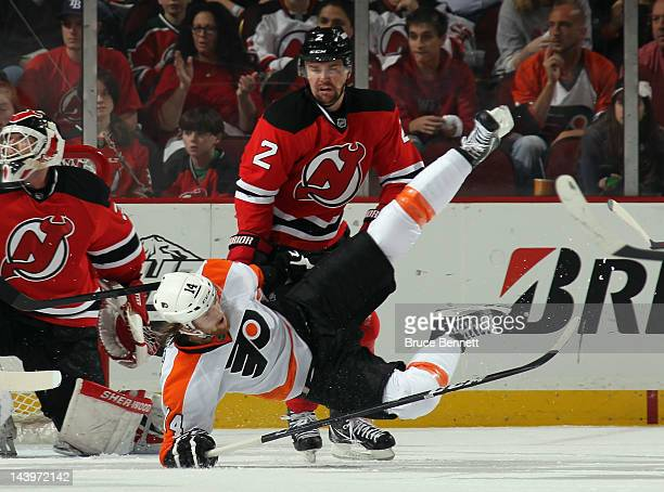 Marek Zidlicky of the New Jersey Devils takes a first period penalty for interference against Sean Couturier of the Philadelphia Flyers in Game Four...