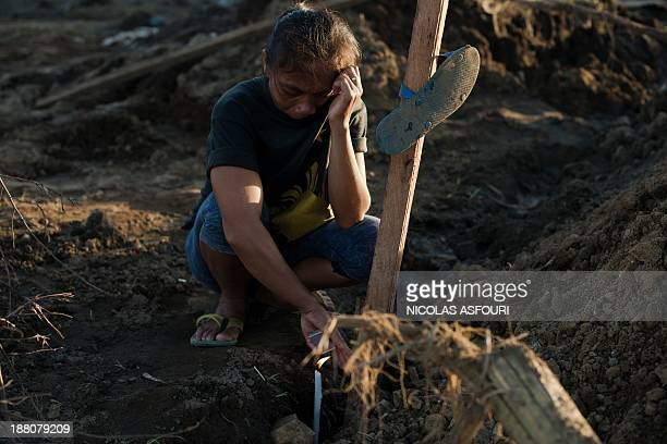 Marelom Cassanares with five children and no home cries at the grave of her husband in the aftermath of Super Typhoon Haiyan in Palo, the outskirts...