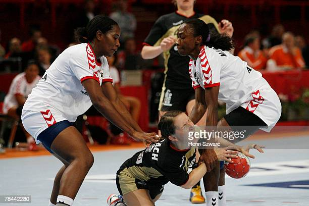 Maren Bambach of Germany is attacked by two players of Angola during the Women's Handball World Championship quarter final match between Germany and...