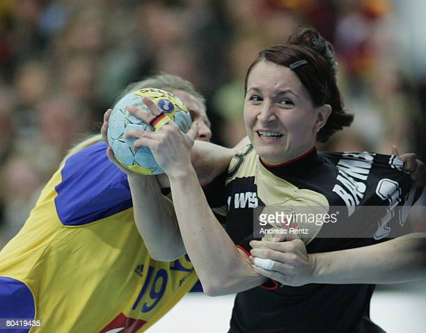 Maren Baumbach of Germany is challenged by Johanna Ahlm of Sweden during the women's handball Olympic qualification tournament match between Germany...