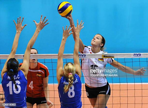 Maren Brinker of Germany pushes the ball above Serbia's Milena Rasic and Ana Antonijevic during their final round match for sixth and seventh place...