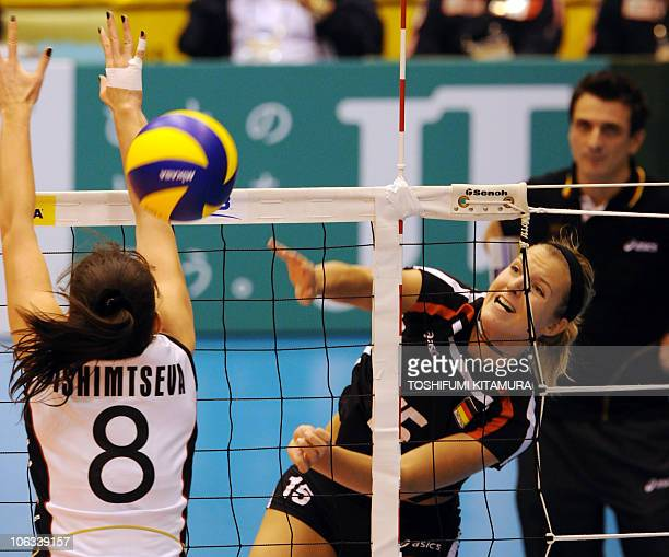 Maren Brinker of Germany spikes the ball through Kazakhstan's setter Korinna Ishimtseva while Germany's Italian head coach Guidetti Giovanni looks on...