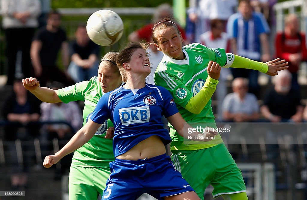 Maren Mjelde of Potsdam (C) goes up for a header against Johanna Tietge (L) and Viloa Odebrecht of Wolfsburg during the Women's Bundesliga match between 1. FFC Turbine Potsdam and VfL Wolfsburg on May 5, 2013 in Potsdam, Germany.
