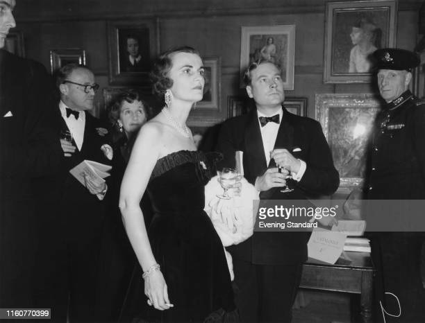 Margaret Campbell, Duchess of Argyll at an exhibition with Mr Lumley-Savile, London, 1st December 1954.