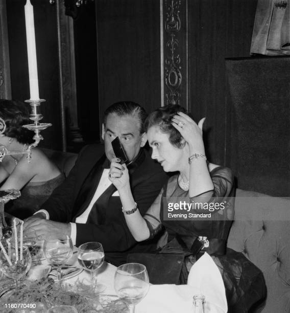 Margaret Campbell, Duchess of Argyll checks her hair in a mirror at a social event, London, 22nd July 1959.