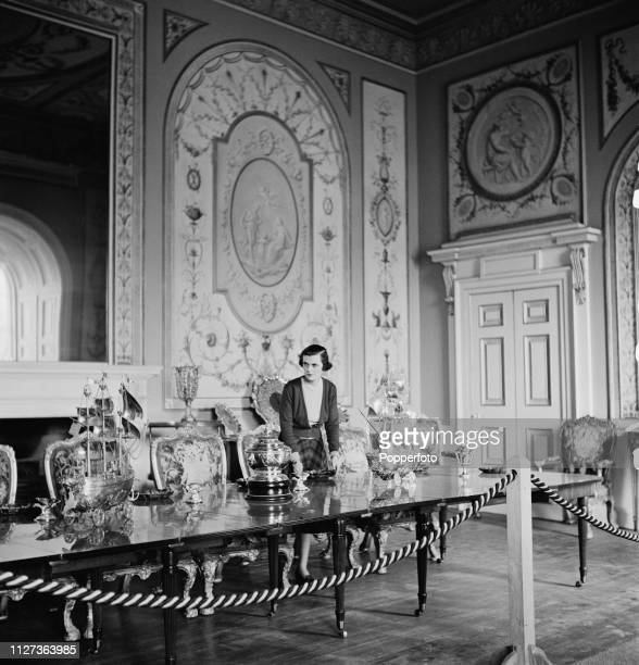 Margaret Campbell, Duchess of Argyll pictured standing with various ornate table pieces at the dining table in the dining room of Inveraray Castle,...